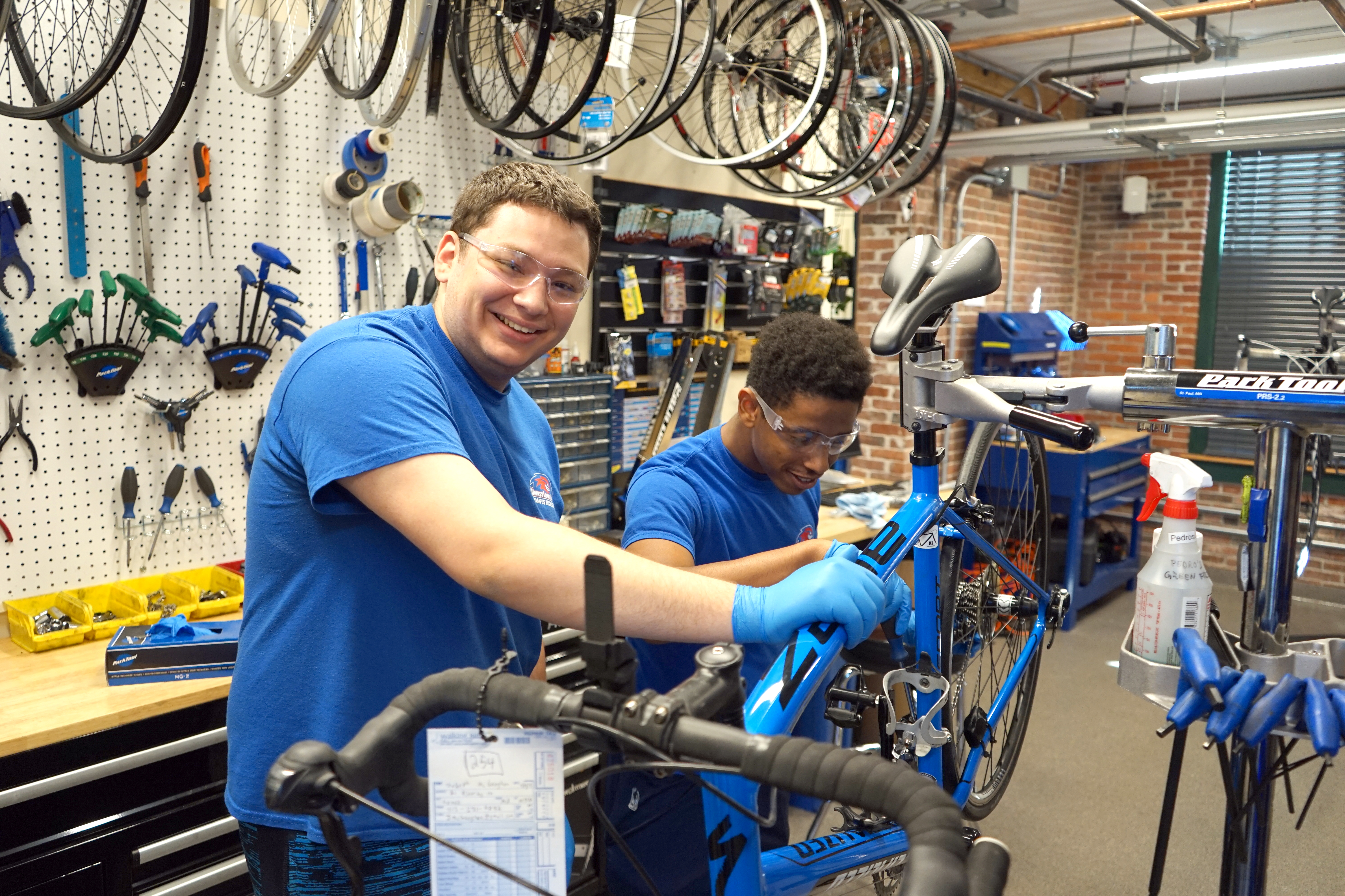 Two smiling student staff members working on a bike