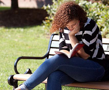 A female student sitting on a bench outside, reading a book.