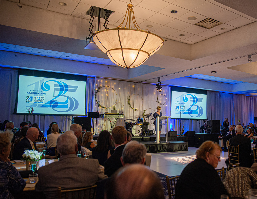 Chancellor Jacquie Moloney speaks in front of a large crowd at UMass Lowell's 125th Anniversary Celebration gala
