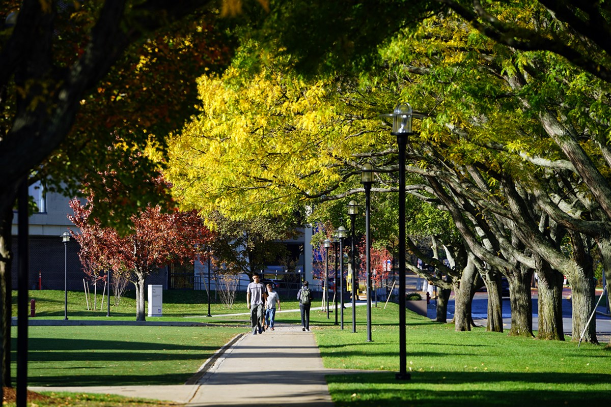 Students walk outside on East Campus among colorful trees