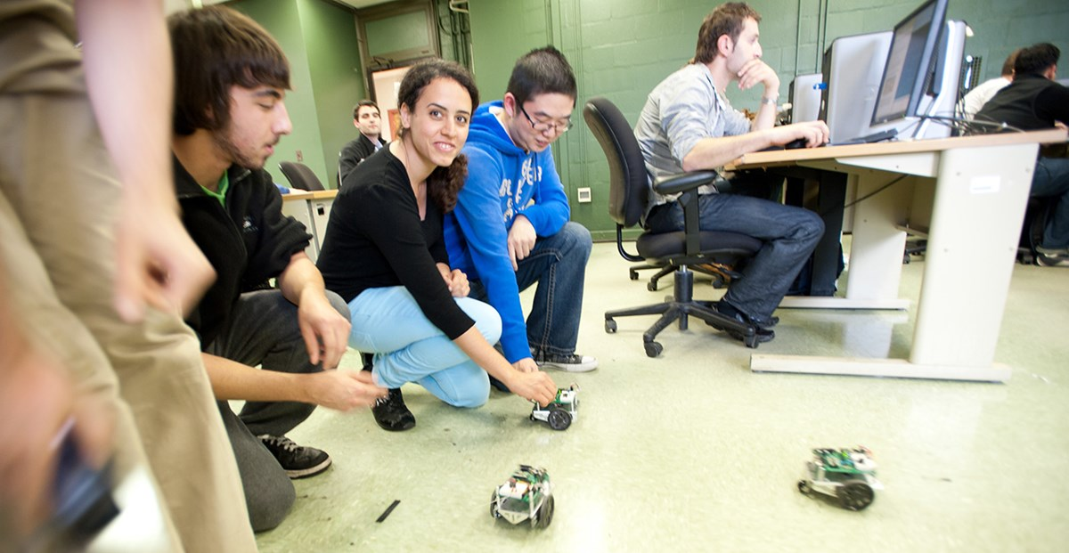 Electrical and Computer Engineering students showing off robots they built