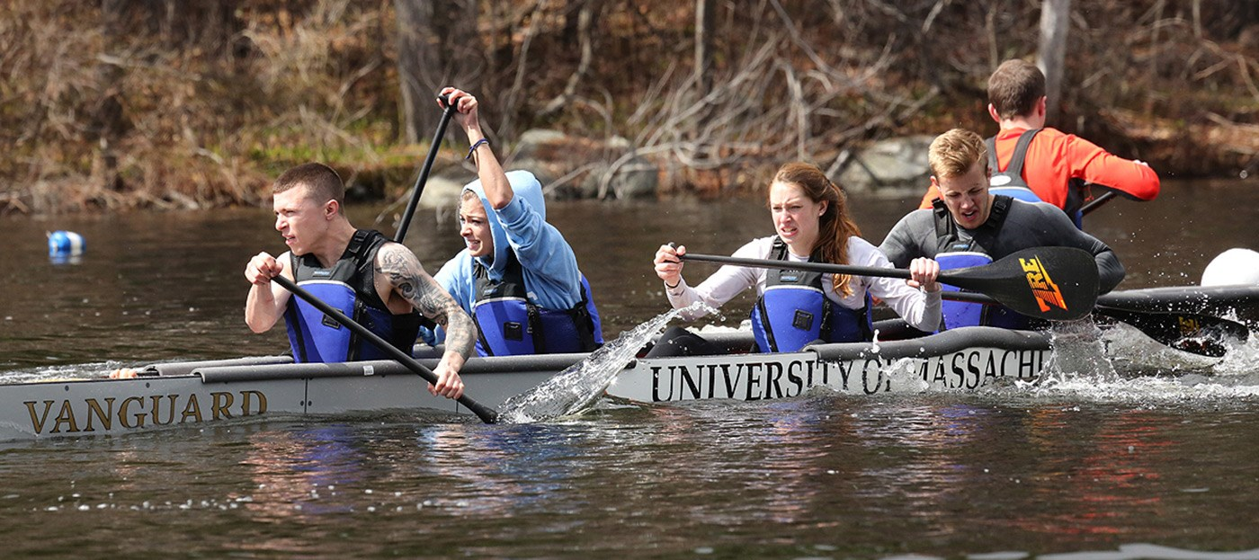 "Timothy Roberts, Natalie Melconian, Rebecca Gonsalves-Lamontagne, and Zachary Morris paddle UMass Lowell's concrete canoe, named ""Vanguard"" during the 2014 regional competition."