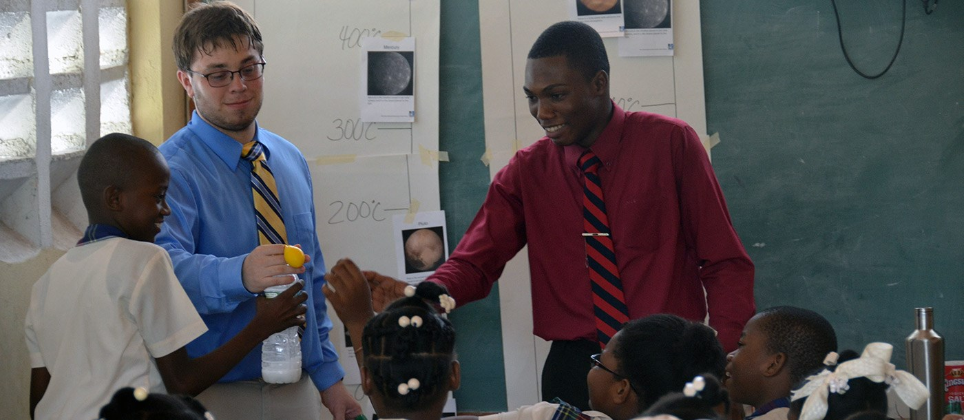 Two UMass Lowell male students doing a science demonstration for a classroom full of young Haitian children on a visit to Haiti in 2016.