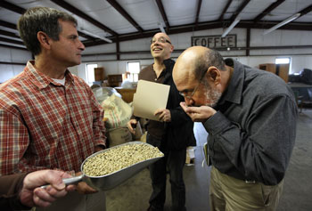 Raul Raudales sniffs arabica coffee beans as he and Richard Trubey, center, meet with Red Barn Coffee Roasters President Mark Verrochi to discuss the coffee drying process.