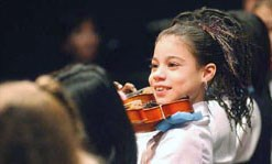 A young girl is smiling and preparing to play the violin with her classmates.