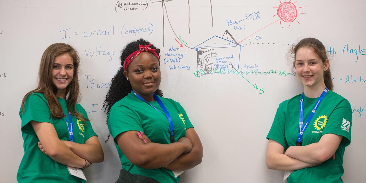 Three women standing in front of a white board at engineering camp
