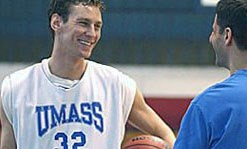 A umass lowell basketball member smiling and talking to a umass lowell student.