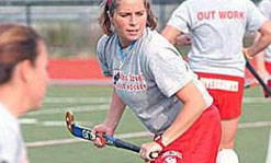 A female field hockey member getting ready to make her move in a field hockey game.