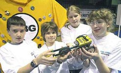 Middle school students hold a robot made of legos