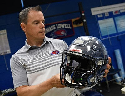 UMass Lowell Prof. Erik Swartz with football helmet equipped with sensors