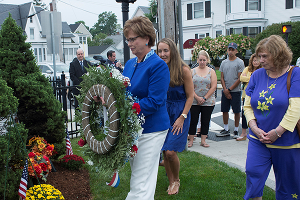 Chancellor Jacquie Moloney places a wreath at Kinney Square in honor of Brian Kinney '95. His widow, Alison Lewandowski and his mother, Darlene Kinney, flank the chancellor.