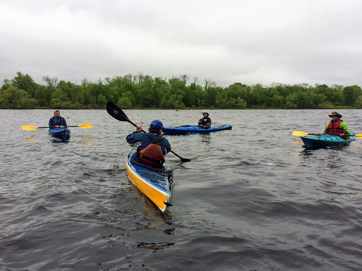 Three people in kayaks watching kayaking instructor
