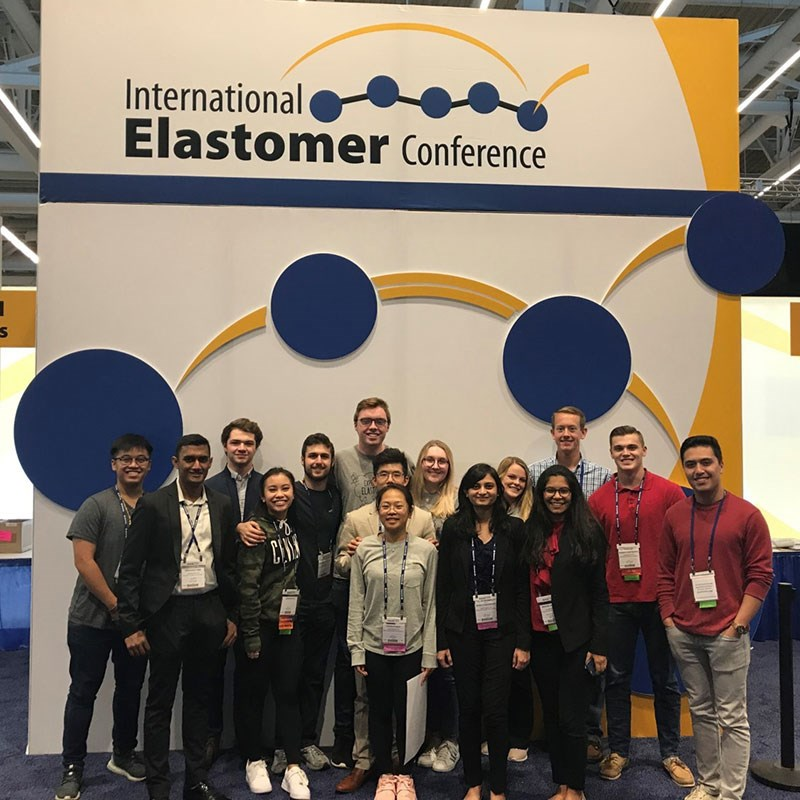 Group of students in front of International Elastomer Conference sign