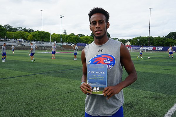"Abdi Shariff-Hassan holds the book ""One Goal"" on the soccer field"