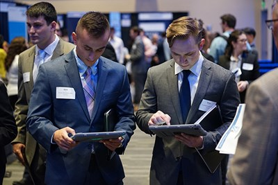 Two students enter information on tablets at the accounting career fair