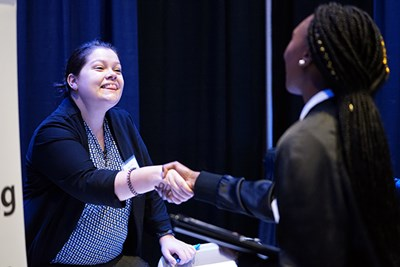 A recruiter shakes hands with a student at the accounting career fair