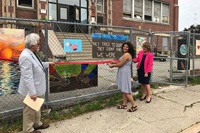 Career Academy student Kiara West cuts the ribbon on an art fence created by students during a day of community service.