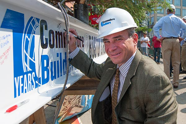 Joseph J. Albanese '84, the president and CEO of Commodore Builders, signs the steel beam during the topping-off ceremony for the four-story 375 Newbury Street building in Boston in 2013.