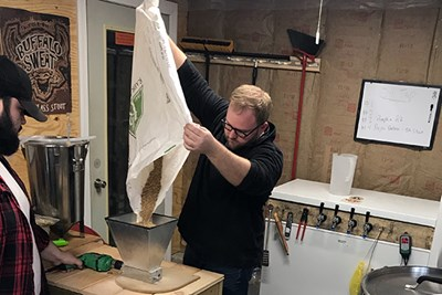 Steffen Johnson pours ingredients while brewing beer