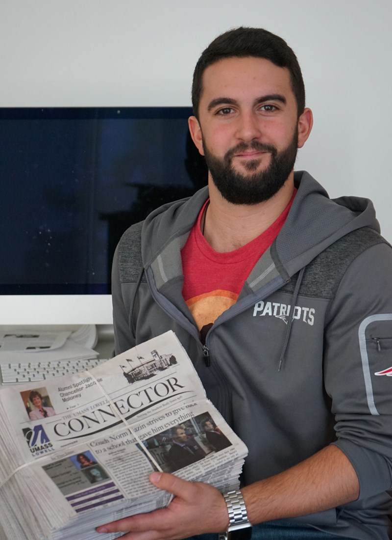 Headshot of Andrew Sciascia holding a stack of The Connector newspapers