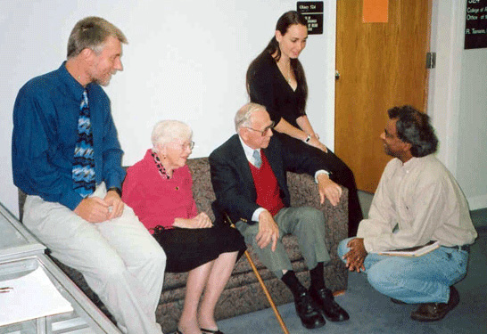 "Mr. Arthur Zamanakos is seated with his wife, Alice, at his right. They are chatting with Raj Prasad, James (""Kiwi"") Graham-Eagle, and a math major."