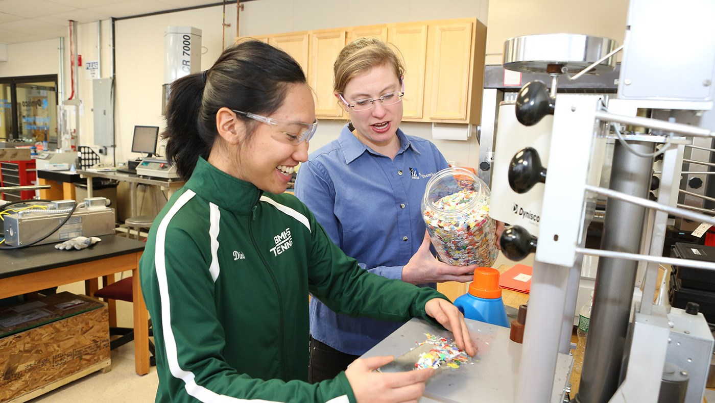 Asst. Prof. Meg Sobkowicz-Kline demonstrating things to a female student in the plastics recycling lab.