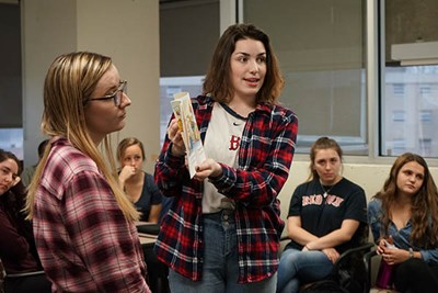 Undergraduate education major Sarah Robinson monitors her virtual students' behavior while MacKenzie Ozaroff reads a book in a teaching practice session with Mursion avatars at UMass Lowell.