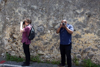 Two students each hold a camera and take a photo facing different directions against a large rock