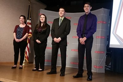 Honors business students on stage presenting at BAE Systems