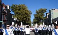 umass lowell's band group playing their instruments and marching on the streets.