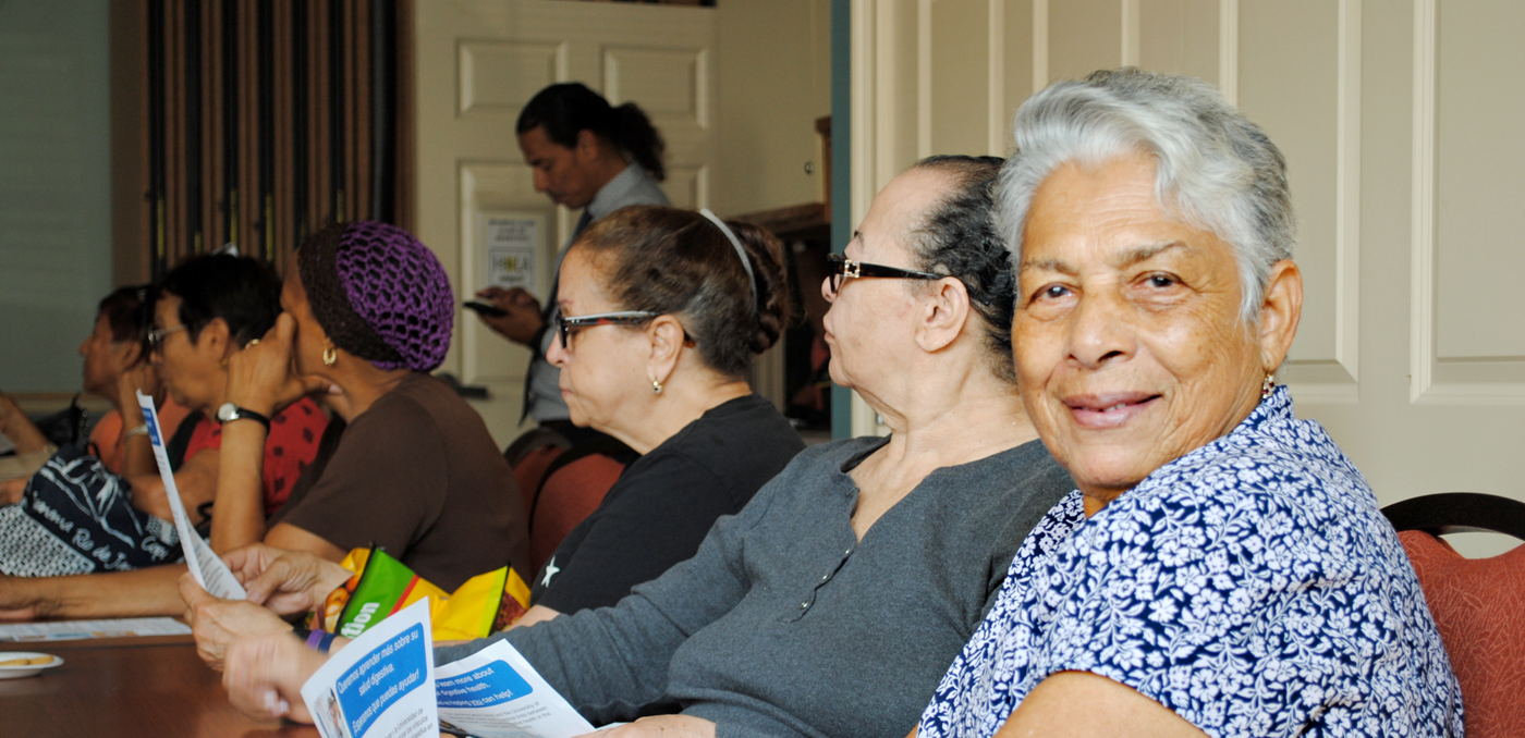 Old lady sitting around the table smiling and looking straight to the camera