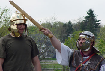History student Evan Giannakas helps Neal Bourbeau, educational programs manager at Higgins Armory Museum, demonstrate the efficiency of ancient Roman helmets at a recent demonstration at UMass Lowell.