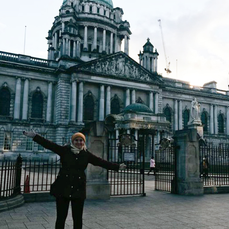 Student standing in front of Belfast City Hall in Ireland