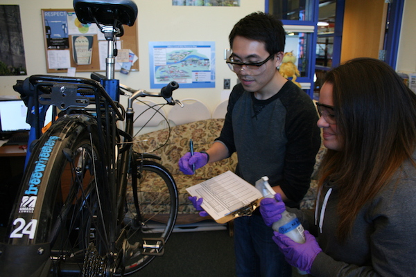 Chemical engineering major George Liang and chemistry major Sabrina Apel tested the performance of safer cleaning products on chains, gears and brakes in the campus bike shop.