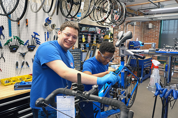Students repair a bicycle in the new bike workshop