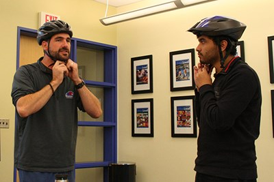 Kevin Soleil helps Hannan Shafiq fit a bike helmet