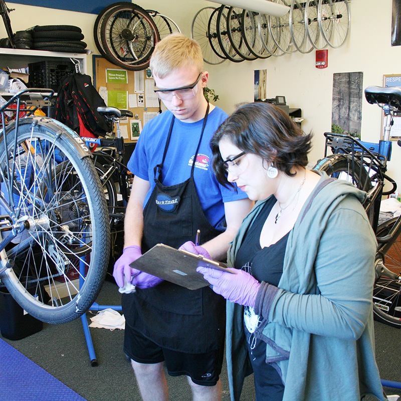 Woman filling out work order in bike shop