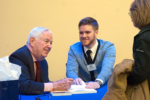 Bill Cummings signs a copy of his book while business student Josiah Gennell lends a hand at University Crossing.