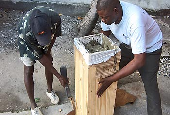 Staff members in the Haiti Development Studies Center in Les Cayes construct a bio-sand water-filter system.