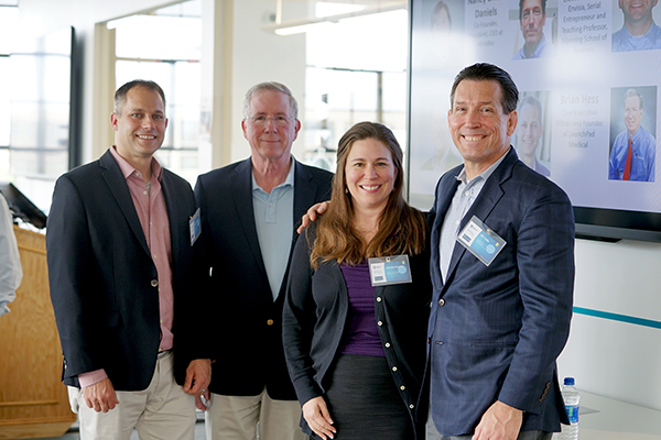 Asst. Prof. Denise Dunlap poses with alum Bill Yelle, right, and panelists Brian Hess and Assoc. Prof. Carl Lawton during the Biotech East visit to M2D2.
