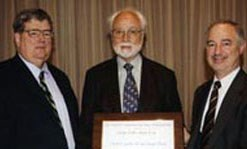 Bodo Reinisch, an environmental professor, holding a NASA award with two other members.