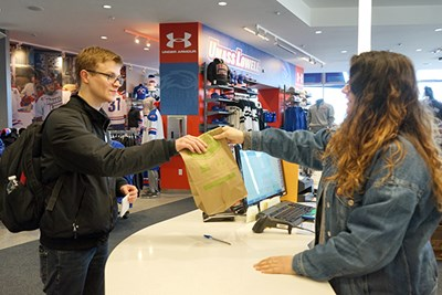 Cashier Danielle DePalma hands a student a paper bag at the bookstore