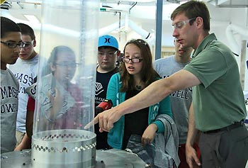 Plastics engineering Asst. Prof. Stephen Johnston, right, demonstrates to members of the Boys and Girls Club of Greater Lowell one of the equipment at the Saab Emerging Technologies and Innovation Center.