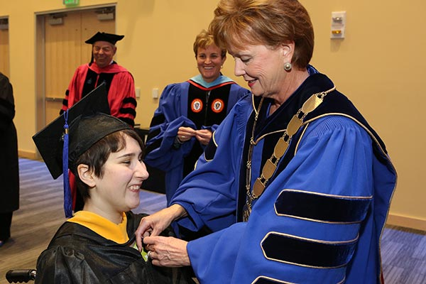 New graduate Brianna Gainley receives a pin from Chancellor Jacquie Moloney during a special Commencement ceremony at University Crossing.