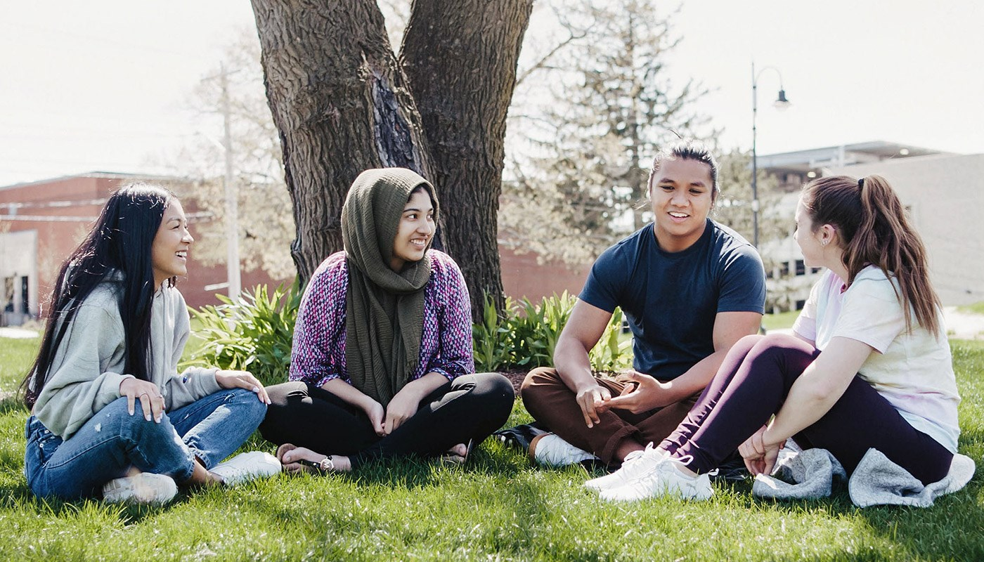 Four students sitting on the ground in front of a tree