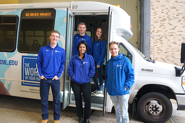 Manager of Parking & Transportation Karina Cruz, center, poses alongside a shuttle with CDL trainers, from left, Justin Wadsworth, Nathan Klosowski, Caitlin Mitchell and Jake Swain.
