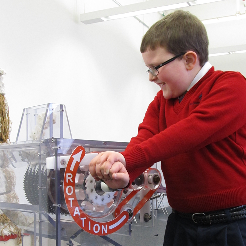 A boy cranking a mock cotton gin at the Tsongas Industrail History Center