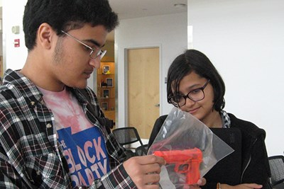 Students inspect a toy gun that's an exhibit in the CSI: Lowell fictional crime contest