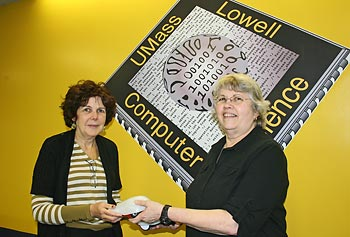 Computer science teacher Jeanne Kendall of Lowell High School, right, receives Finch robots from Phyllis Procter, manager of UMass Lowell's Community Partnership Program.