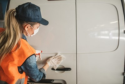 A worker wearing PPE cleans a food delivery van.